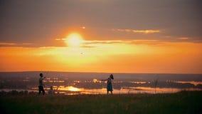 Junge Frau und ihr Ehemann, die Badminton auf dem Feld, stehend nahe bei ihrem kleinen Sohn, Sonnenuntergangsommerabend spielt stock video footage