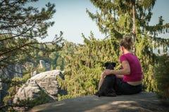 Junge Frau und ihr Hund genießen Bergwanderungen im Sommer lizenzfreie stockfotos