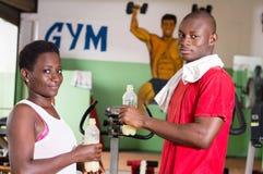 Junge Frau und ihr Trainer halten Flaschen Fruchtsaft in der Hand Stockbild