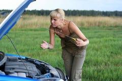 Junge Frau und ihr unterbrochenes Auto Stockbild