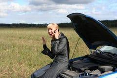 Junge Frau und ihr unterbrochenes Auto Stockfoto