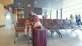 Junge Frau und ihre kleine Tochter haben zusammen Rest im Warteraum am Flughafen stock footage