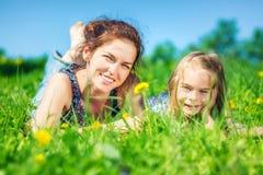 Junge Frau und ihre Tochter auf grünem Sommergras stockbild