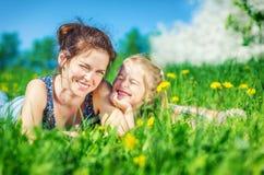 Junge Frau und ihre Tochter auf grünem Sommergras stockfoto