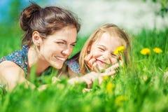 Junge Frau und ihre Tochter auf grünem Sommergras stockbilder