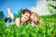 Junge Frau und ihre Tochter auf grünem Sommergras lizenzfreie stockfotografie