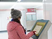 Junge Frau und Informationen fragen Maschine in der U-Bahn Stockfotografie