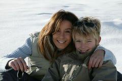 Junge Frau und Junge im Schnee Stockbilder