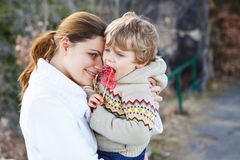 Junge Frau und kleine der Sohn, die am Abend umarmt, beleuchten Lizenzfreie Stockfotografie