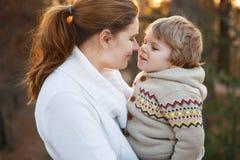 Junge Frau und kleine der Sohn, die am Abend umarmt, beleuchten Stockfotografie