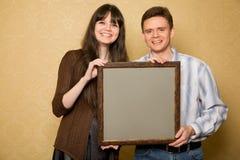 Junge Frau und lächelnder Mann mit Abbildung im Feld Lizenzfreies Stockfoto