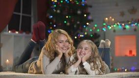 Junge Frau und Mädchen, die unter dem Weihnachtsbaum, lächelnd zur Kamera, Feiertage nuzzling ist stock video