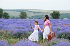 Junge Frau und M?dchen gehen durch das Lavendelblumenfeld, sch?ne Sommerlandschaft lizenzfreies stockbild