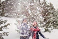 Junge Frau und Mann, die mit Schnee spielt Stockfotos
