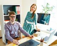 Junge Frau und Mann, die vom haus- modernen Geschäftskonzept arbeitet Stockfotografie