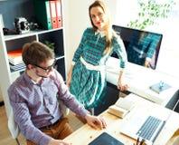 Junge Frau und Mann, die vom haus- modernen Geschäftskonzept arbeitet Stockfoto