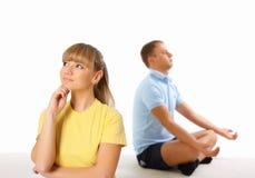 Junge Frau und Mann, die Yoga im Hintergrund tut Stockbilder