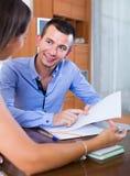 Junge Frau und Mann mit Finanzdokumenten in der Agentur Stockfotos