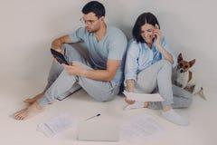 Junge Frau und Mann sitzen zurück zu einander, tun Konten zusammen, machen die notwendigen Berechnungen, umgeben mit Papierdokume lizenzfreie stockfotografie