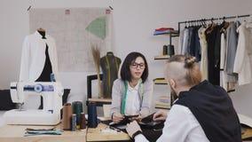 Junge Frau und Mannmodedesigner oder -schneider, die mit den grauen Geweben sitzen im schönen Büro mit arbeiten stock video