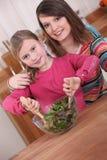 Junge Frau und mischender Salat der Tochter lizenzfreie stockfotografie