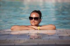 Junge Frau und Pool stockfotos