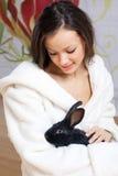 Junge Frau und schwarzes Kaninchen Lizenzfreie Stockbilder