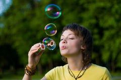 Junge Frau und Seifeluftblasen Stockfotos