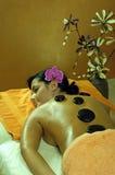 Junge Frau und Stein-Massage Stockfotografie