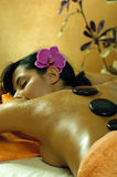 Junge Frau und Stein-Massage Stockfotos