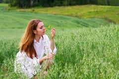 Junge Frau und wilde Blume. Lizenzfreies Stockfoto