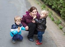 Junge Frau und zwei kleine Jungen, die Eiscreme essen Stockbild