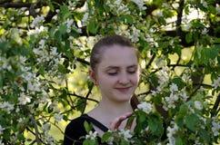 Junge Frau unter den blühenden Niederlassungen eines Apfelbaums, Frühling Lizenzfreies Stockfoto