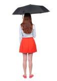 Junge Frau unter einem Regenschirm Stockfotos