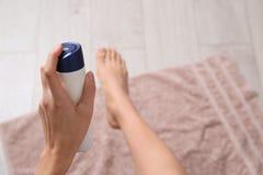 Junge Frau unter Verwendung des desodorierenden Mittels für Füße zu Hause lizenzfreie stockfotos