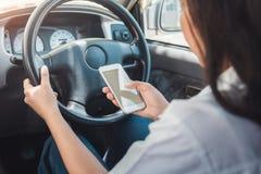 Junge Frau unter Verwendung des intelligenten Telefonweileautofahrens lizenzfreie stockfotografie