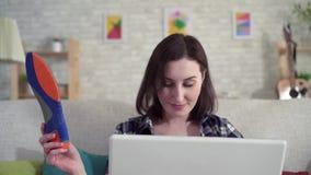 Junge Frau unter Verwendung des Laptops und der Suchen das Internet zu Information über orthopädische Einlegesohlen stock footage