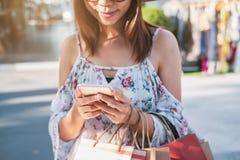 Junge Frau unter Verwendung des Smartphone mit Einkaufstaschen und Kreditkarte am Einkaufszentrum lizenzfreie stockfotografie