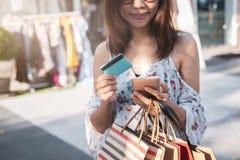 Junge Frau unter Verwendung des Smartphone mit Einkaufstaschen und Kreditkarte am Einkaufszentrum stockfoto