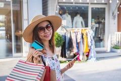 Junge Frau unter Verwendung des Smartphone mit Einkaufstaschen und Kreditkarte am Einkaufszentrum lizenzfreie stockbilder