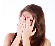 Junge Frau versteckt ihr Gesicht in ihren Palmen Stockfoto