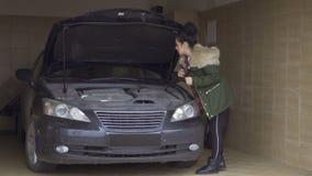 Junge Frau versucht, den Automotor mit Schlüssel zu reparieren stock video footage