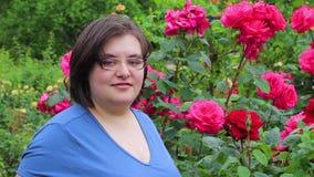Junge Frau vor einem Rosenbusch stock footage