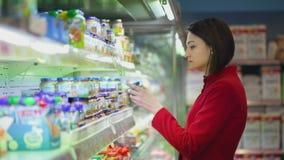 Junge Frau wählt die Waren auf einem Schaukasten stock footage
