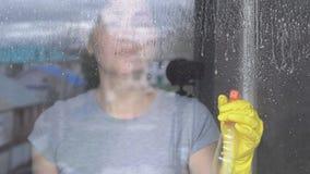 Junge Frau wäscht ein Fenster in den gelben Handschuhen mit einem Reiniger stock footage
