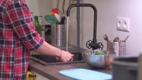 Junge Frau wäscht Gemüse im Spülbecken stock video footage