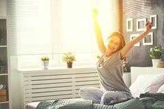 Junge Frau wachte morgens im Schlafzimmer durch das windo auf stockbild