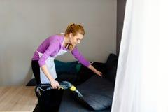 Junge Frau in waschendem Sofa des Schutzblechs mit Vakuumwaschmaschine lizenzfreie stockfotos