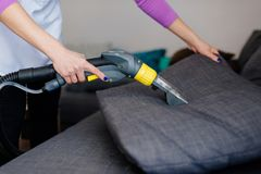 Junge Frau in waschendem Sofa des Schutzblechs mit Vakuumwaschmaschine lizenzfreies stockfoto