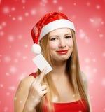 Junge Frau in Weihnachtsmann-Hut mit Weihnachtskarte Lizenzfreie Stockfotografie